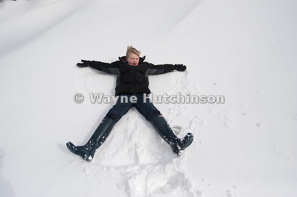 Boy making snow angels in snowdrift, Cumbria, UK