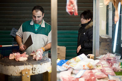 Greece - Athens - A butchers chops a carcass of meat for a woman customer in the Athens Central Market on Athinas Street.