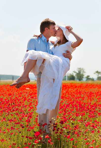 Couple kissing in field of poppies