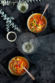 Bowls of Sesame Lentil Soup topped with roasted red peppers and chives.