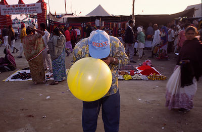A man blows up a baloon at a market for pilgrims. Ardh Kumbh Mela 1995, Allahbad, India