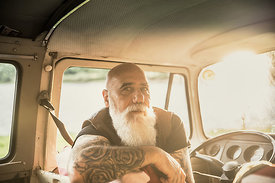 Portrait of a senior hipster inside their vintage van
