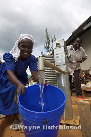 Woman in blue dress collecting water from new pump in village, western Kenya Africa