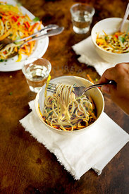 A woman is eating Asian Sesame Pasta Salad served with white wine. Photographed on a brown/black background.