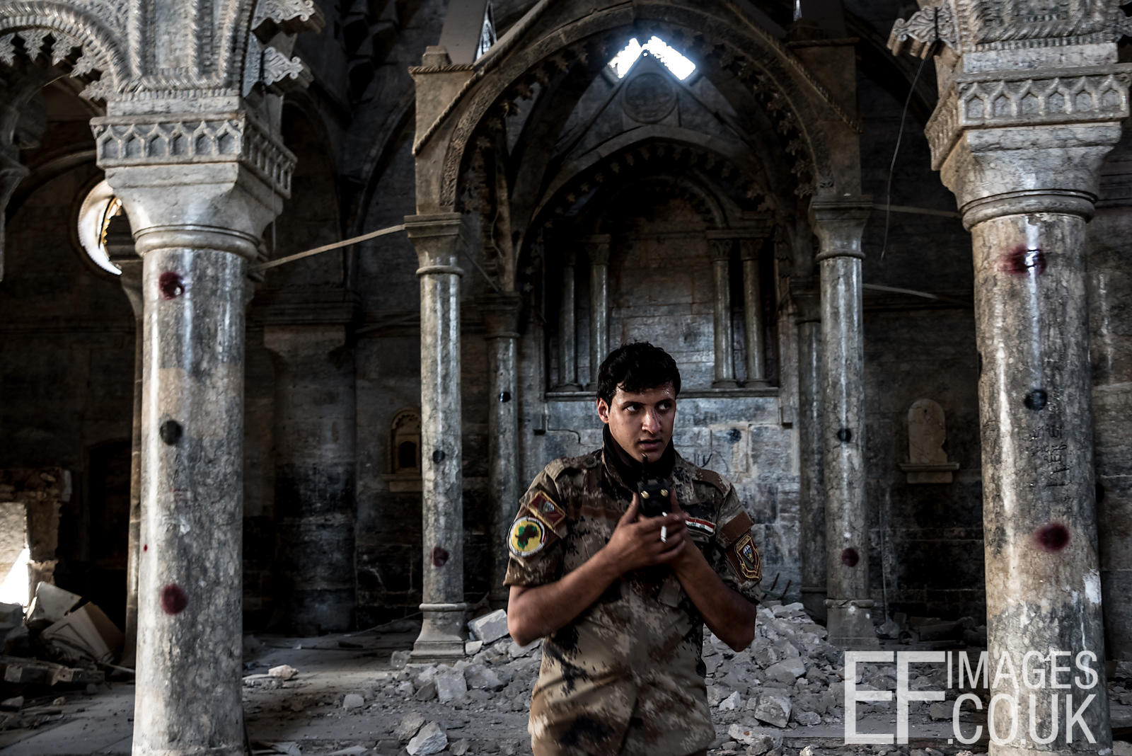 An Iraqi Special Forces Soldier talks on his radio inside the Church of St Thomas, used as an ISIS base until its liberation. Old City of West Mosul, Iraq. 24 June 2017