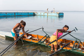 Teenage girls from a rowing club getting a boat - scull - ready for a practice in Cienfuegos, Cuba.