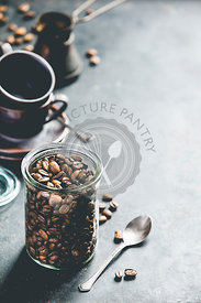 Coffee composition on dark background. Coffee beans in glass jar, coffee cups and old metallic coffee maker. Copyspace, food frame concept