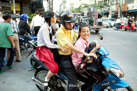 A Thai family gathers on their motor bike, the youngest member smiles for the camera.
