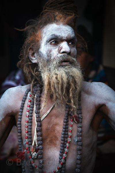 A Naga Sadhu (holy man) smokes a pipe and meditates at a staging area in Kolkata, India for pilgrims going to the Gangasagar Mela on Sagar Island south of Kolkata.