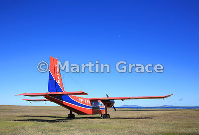 FIGAS (Falkland Islands Government Air Service) Britten-Norman Islander Aircraft VP-FBM on the ground at Carcass Island airstrip, Falkland Islands. Moon is visible in a clear blue sky.