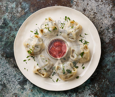 Traditional steamed dumplings Manti with Tomato sauce