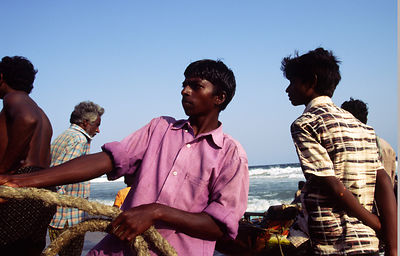 Fisherboy pulls at a rope, Puri beach, India
