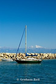 yacht moored in new harbour, with the mountains of albania in the distance, san stefanos, north west, corfu, ionian islands, greece.