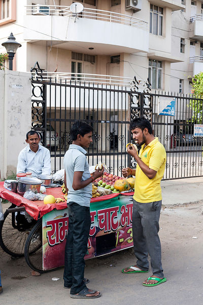 India - Gurgaon - Residents buy fruit and tea from vendors outside their gated community