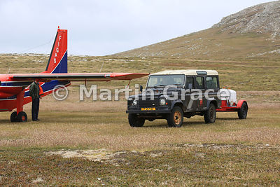 Rear of FIGAS Britten-Norman aircraft with the landrover-drawn fire tender on the grass airstrip at Carcass Island, Falkland Islands