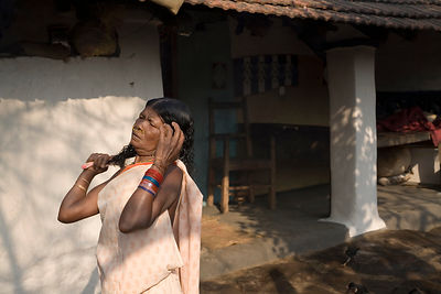 A tribal woman combs her hair