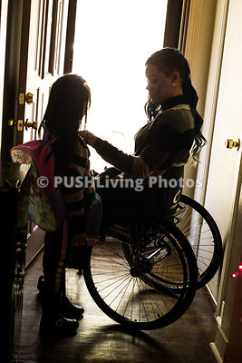 Young mother in a wheelchair preparing her daughter for school