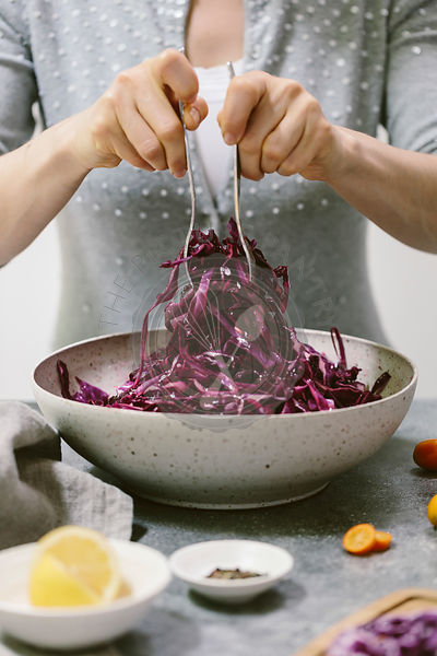 A woman is photographed as she is mixing a red cabbage salad