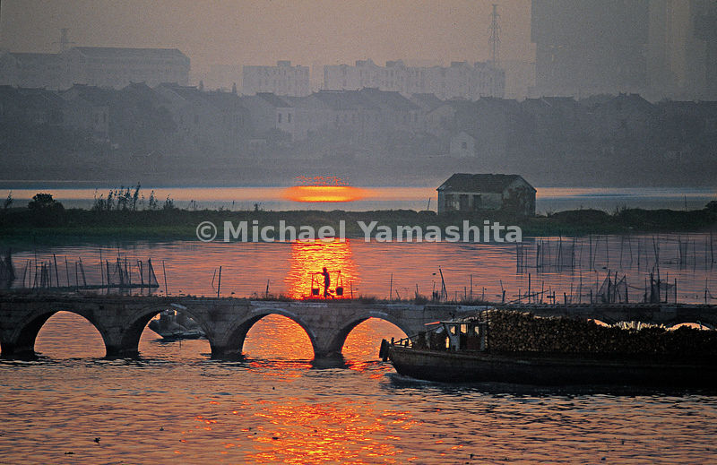 Sunset in Suzhou sets the water of the Grand Canal alight.