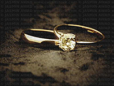 Wedding rings with solitaire diamond on black velvet background with copy space