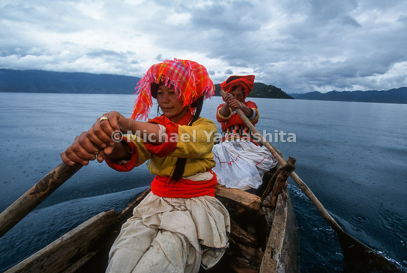 Mosuo women row to Lamasary Island. Old Lamasary was destroyed by the Red Guard.