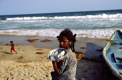 Child selling fish, Puri beach, India