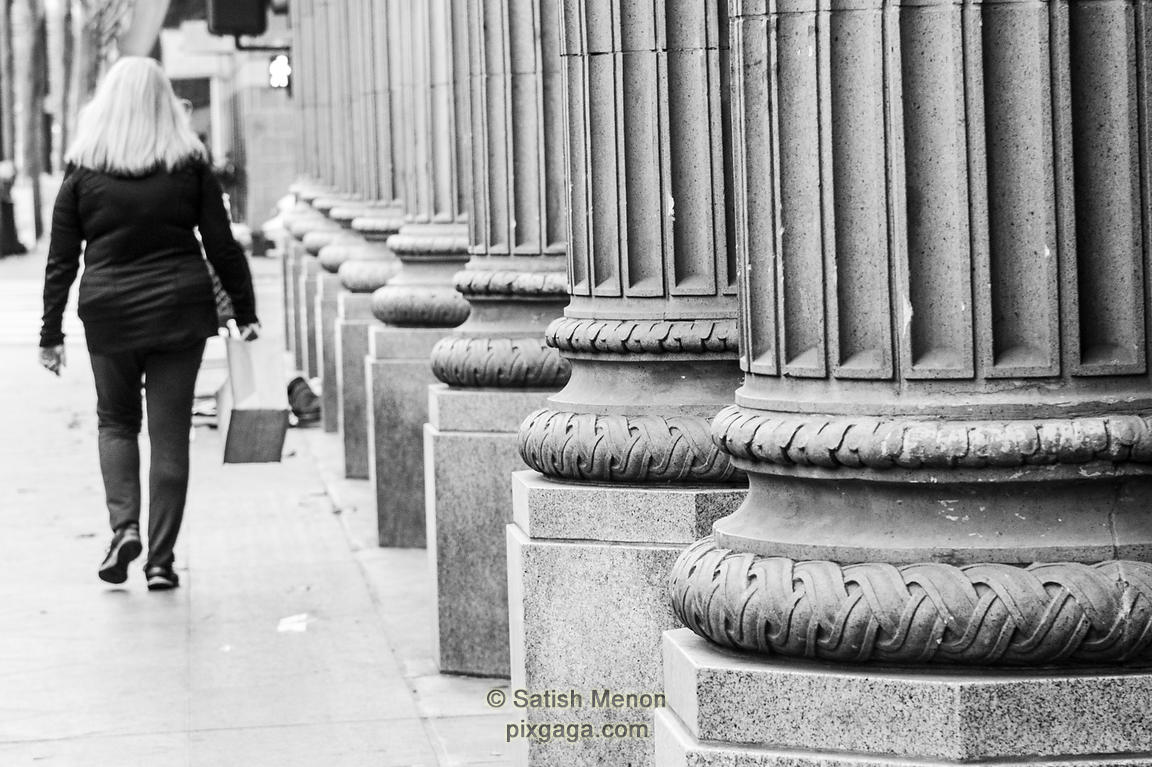 Woman walking along pillars, San Jose, CA, USA