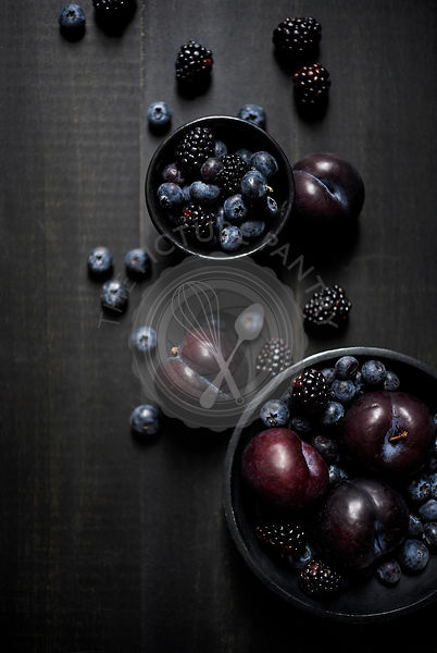 Bowls of blue and black fruits laid out artistically and beautifully on a dark wood surface. Dark and moody.