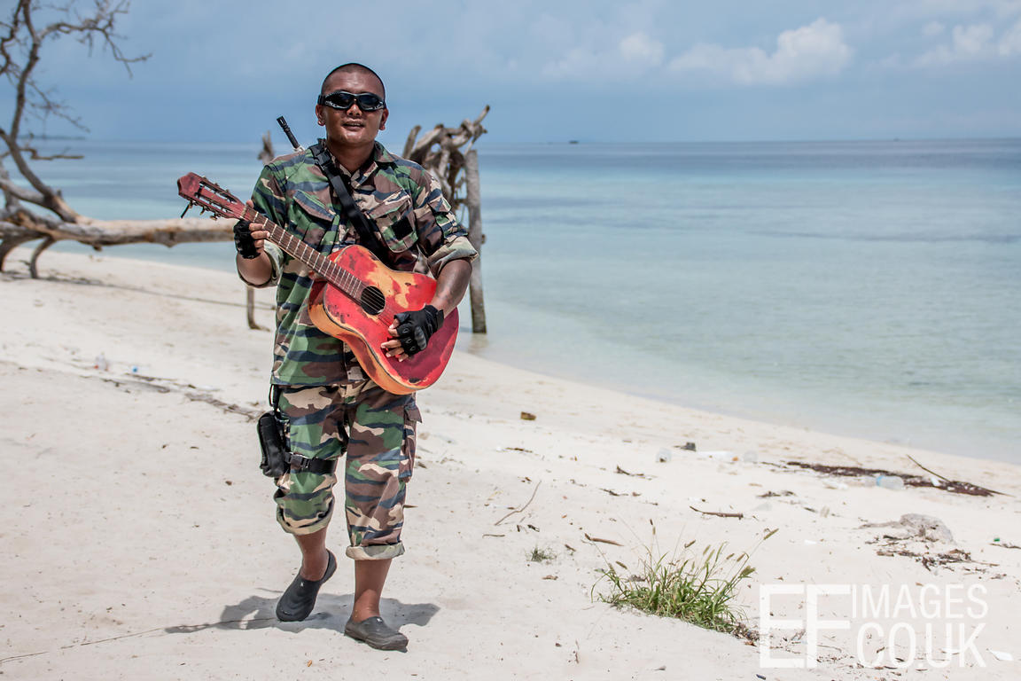 Man With Guitar And Gun Walking Along A Tropical Beach