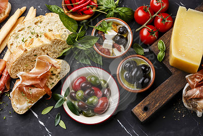 Italian snacks food with Ham, Sliced bread Ciabatta, Olives, Feta cheese with dried tomatoes and Parmesan cheese on dark marble background