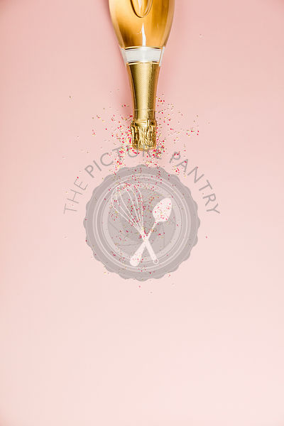 Flat lay of Celebration. Champagne bottle with sprinkles on pink background.