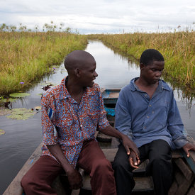 Kalenga Kangoba, who has been blind for twelve years is comforted by his brother Komba aboard a small pirogue that will take them back to their home in Kashobwe (an island close to The Democratic Republic of Congo). As they set off, Kalenga realises that he can see the flowers of the water-lilies. Shabo Harbour near Nchelenge, Zambia