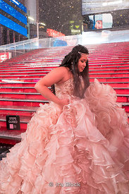 A bride walking on the red steps at Times Square, New York City on a snowy day.