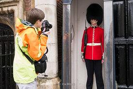 A young tourist taking photos of a Queen's Guard in London, UK.