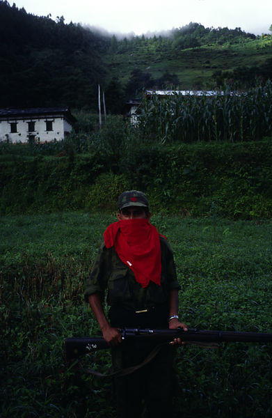 Nepal - Dolakha - a Maoist rebel holds a vintage rifle on patrol at dawn in a field