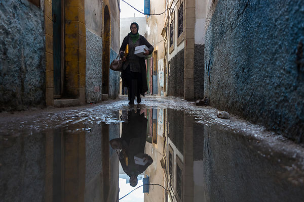 Reflection of a Woman Walking in the Old Medina