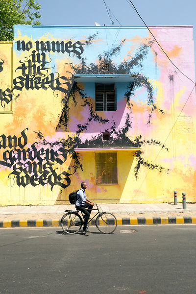 A cyclist passes a painting and poem by Niels Shoe Meulman on display in the Lodhi Colony area of New Delhi