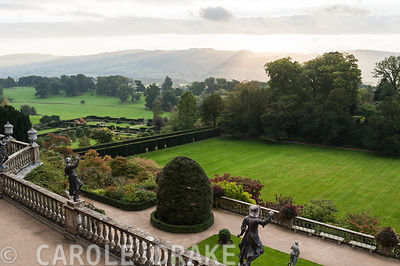 View from the Top Terrace at Powis Castle Gardens giving views across the Great Lawn and the Formal and Fountain Gardens to surrounding landscape and the outline of Y Golfa over which the morning sun is rising