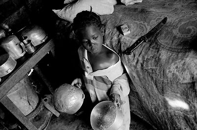 Child with cooking pots, Haiti