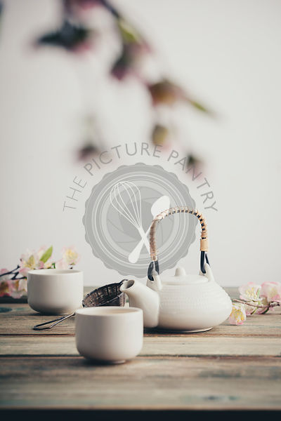 White teapot, cups, sakura flowers on wooden table against the white wall