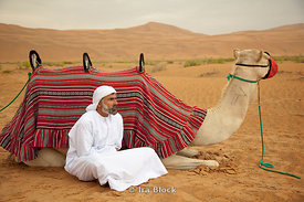 A camel holder taking a rest beside a camel.