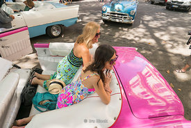 Tourists in an old car in Havana, Cuba.