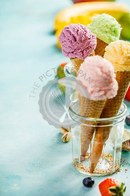 Various of ice cream flavor in cones pink (strawberry, raspberry), purple (blueberry), green (pistachio, green tea, lime) and yellow (mango, banana) setup on blue wooden background . Summer and Sweet menu concept.