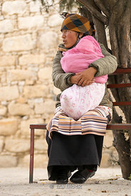 A woman holding a baby at Sera Monastery, Lhasa, Tibet.