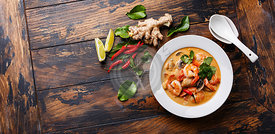 Tom Yam kung Spicy Thai soup with shrimp, seafood, coconut milk and chili pepper in bowl on wooden background copy space