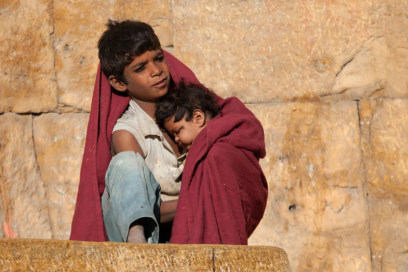A boy sits with his younger brother on a cold morning at the fort in Jaisalmer, Rajasthan, India