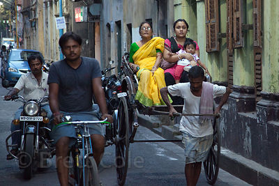 A rickshaw puller pulls a mother, daughter, and grandma down a backstreet in Bowbazar, Kolkata, India.