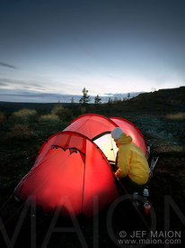 Backpacker and tent by night