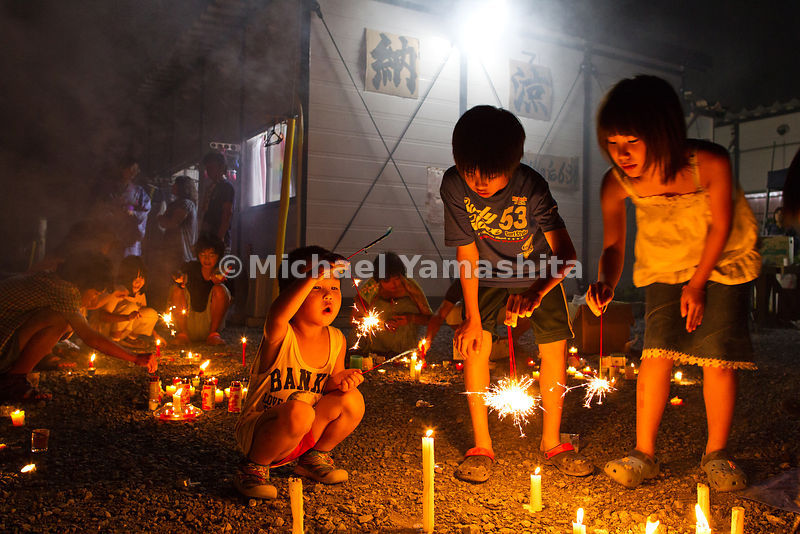 Temporary housing facility at Ofunato Junior High School holds first community get together for Obon. Kids light up sparklers as adults socialize and enjoy food and drinks donated by local businessman.