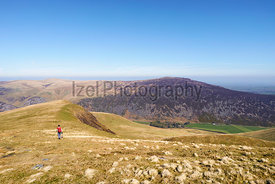 A female hiker walking off the summit of Bowscale Fell in the English Lake District, UK.